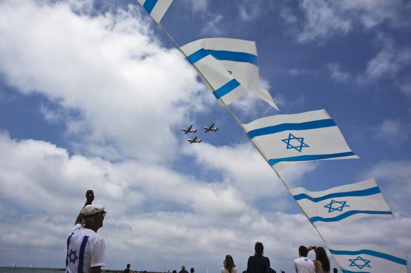 Israelis look on as Israeli air force jets fly in formation over the Mediterranean Sea during celebrations for Israel's Independence Day. Picture by Nir Elias | Reuters