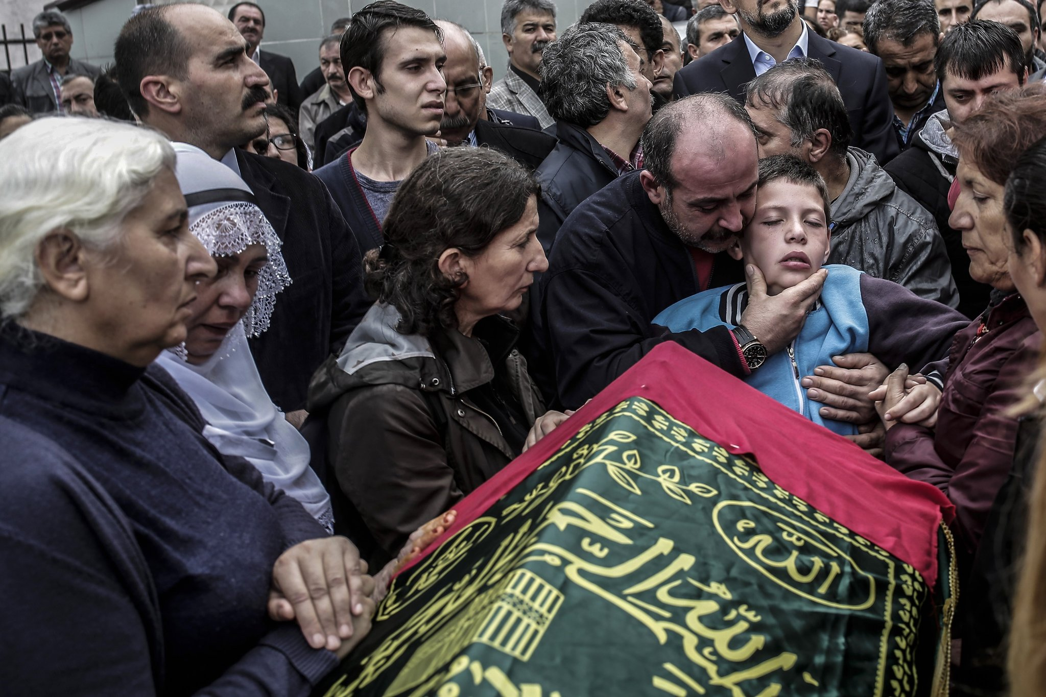 Relatives comfort nine-year-old Cayan Tuylu near the casket of his father Sarigul, a victim of the twin bombings in Ankara the day before, at his funeral in Istanbul on Sunday. Picture by Yasin Akgul | Agence France-Presse/Getty Images