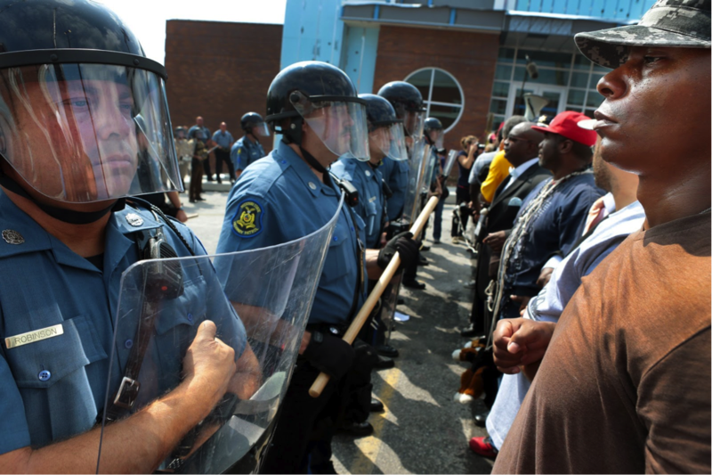Protestor Boss Bastain of St. Louis locks arms with others as they confront Missouri State Highway Patrol troopers in front of the Ferguson police station on Monday, Aug. 11, 2014. Marchers are entering a third day of protests against Sunday's police shooting of Michael Brown. Picture by Robert Cohen | AP Photo/St. Louis Post-Dispatch