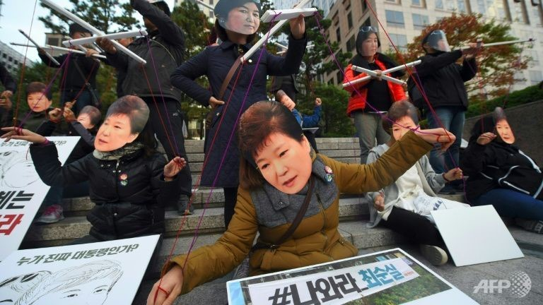 Protesters wearing masks of South Korean President Park Geun-Hye (front) and her confidante Choi Soon-Sil demonstrate at a candle-lit rally in Seoul, on October 29, 2016 AFP/Jung Yeon-Je